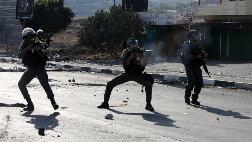 Israeli border guards take aim at Palestinian demonstrators (unseen) during clashes at the Hawara checkpoint, south of the West Bank city of Nablus on Friday.