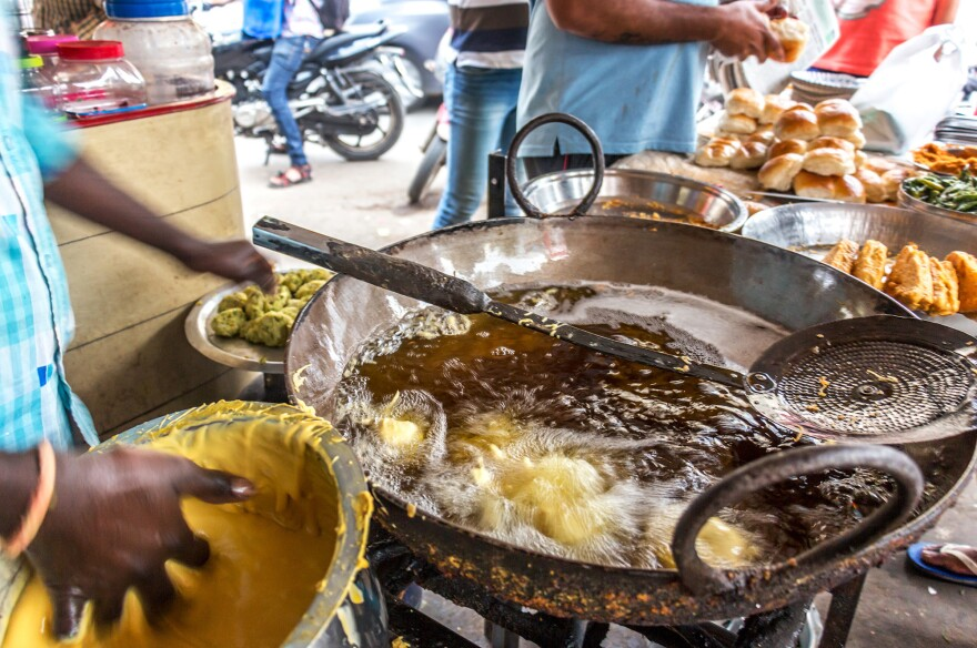 A street vendor frying potato <em>vadas </em>for <em>vada pav </em>in Mumbai's busy Dadar neighborhood.