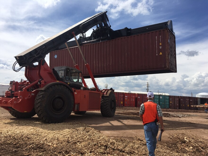 A Rough Terrain Container Handler, or RTCH, moves a shipping container full of about 40,000 pounds of wood chips to a nearby railcar.