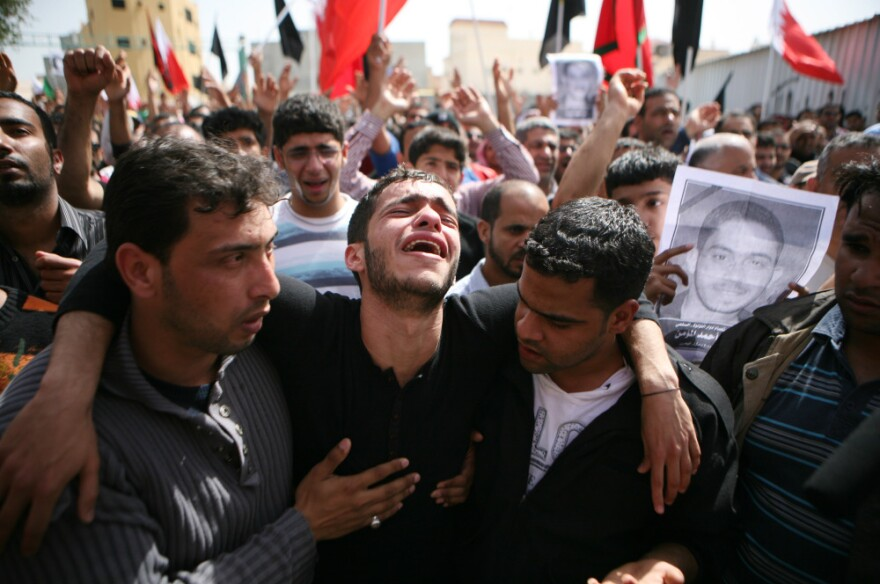 Friends and family members mourn during a funeral for slain anti-government protester Ali Ahmed al Muameen in February in Sitra, Bahrain.
