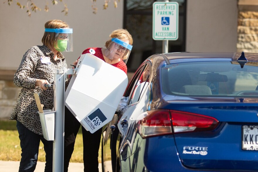 Poll workers assist a driver with curbside voting.