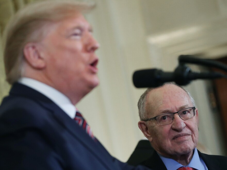 Alan Dershowitz listens to President Trump at a White House event in December. The lawyer will deliver constitutional arguments during Trump's Senate impeachment trial.