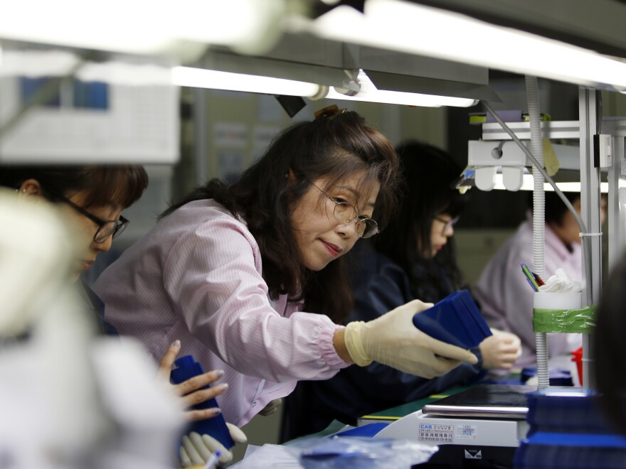 South Korea's parliament has shortened the maximum workweek amid the country's low birth and productivity rates. Workers are seen here at a factory in Ansan, South Korea, in 2015.