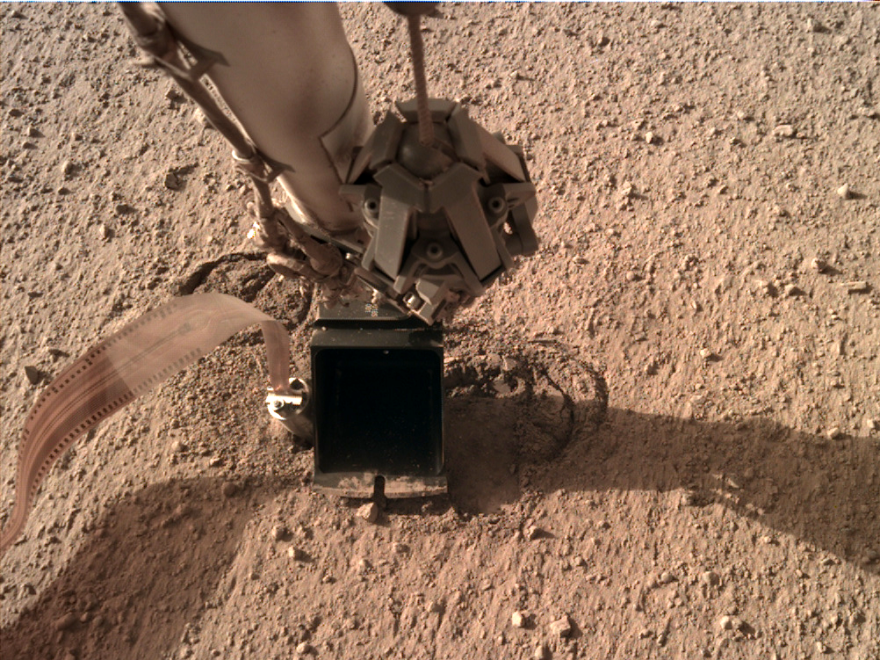 """Instrument Deployment Camera on Mars InSight lander showing scoop """"pinning"""" thermal instrument called the mole."""