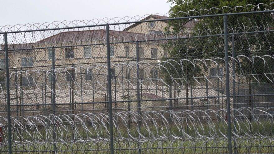 Tents are visible behind wire fences last month near buildings of the Federal Medical Center prison in Fort Worth, Texas. Hundreds of inmates inside the facility reportedly have tested positive for the coronavirus, and several have died.