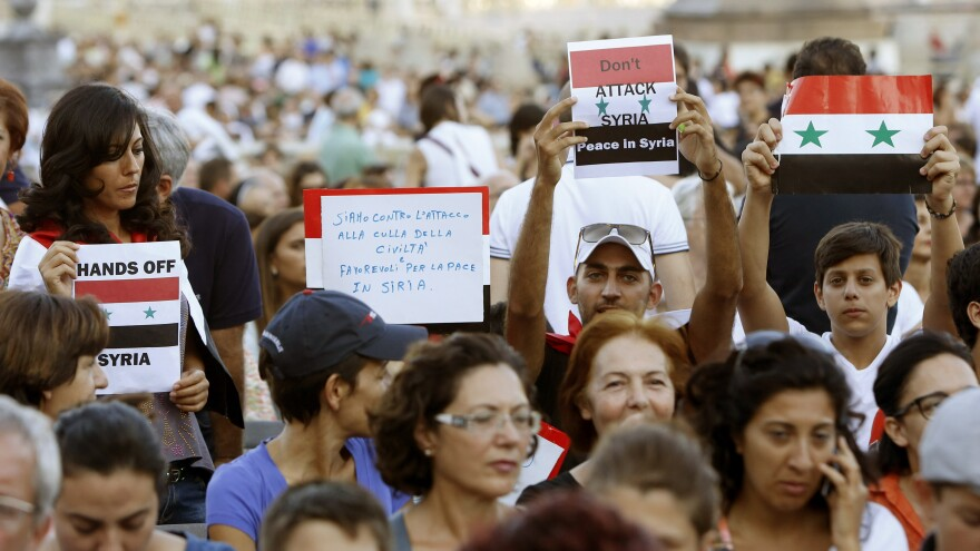 People in St. Peter's Square at the Vatican hold Syrian flags and signs against a possible military strike, after gathering for a vigil in the name of peace convened by Pope Francis Saturday.