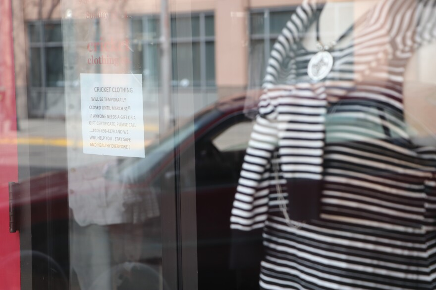 A manequinne in a black and white striped shirt shows in a window with a closed sign behind it.