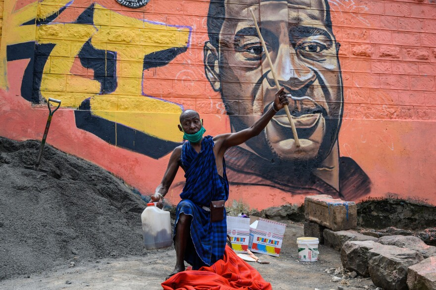 A Maasai man in the Kibera slum of Nairobi, Kenya, prays next to a mural of George Floyd, painted by the artist Allan Mwangi on June 3.