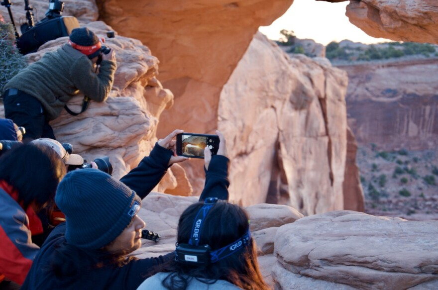 photo of tourists at arch.