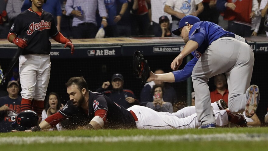 The Indians' Jason Kipnis scores, evading a tag by Jon Lester during the fifth inning.