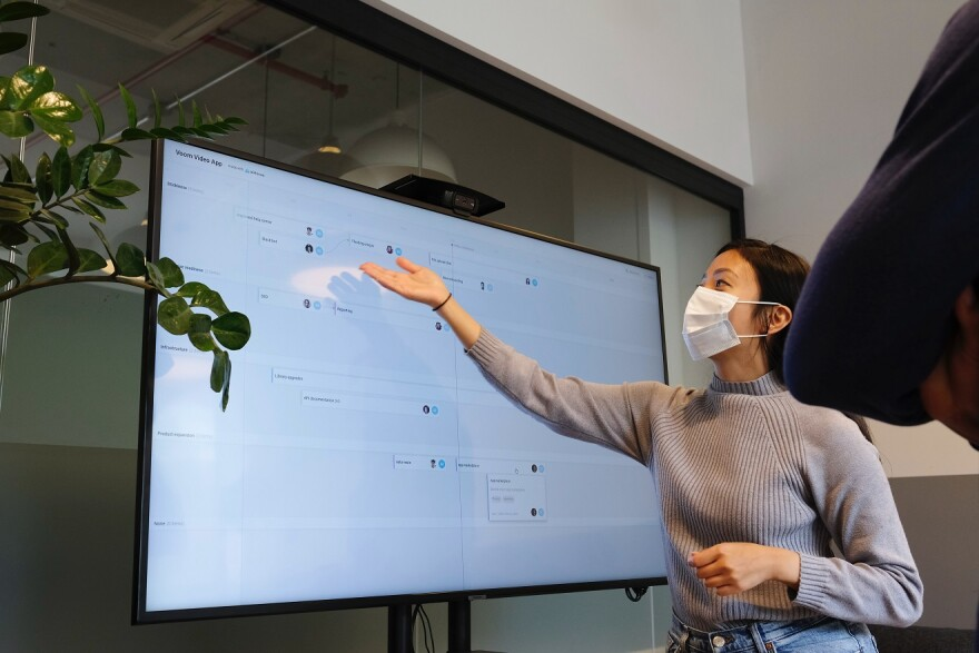 A teacher wears a mask and points to a large monitor with information on it.