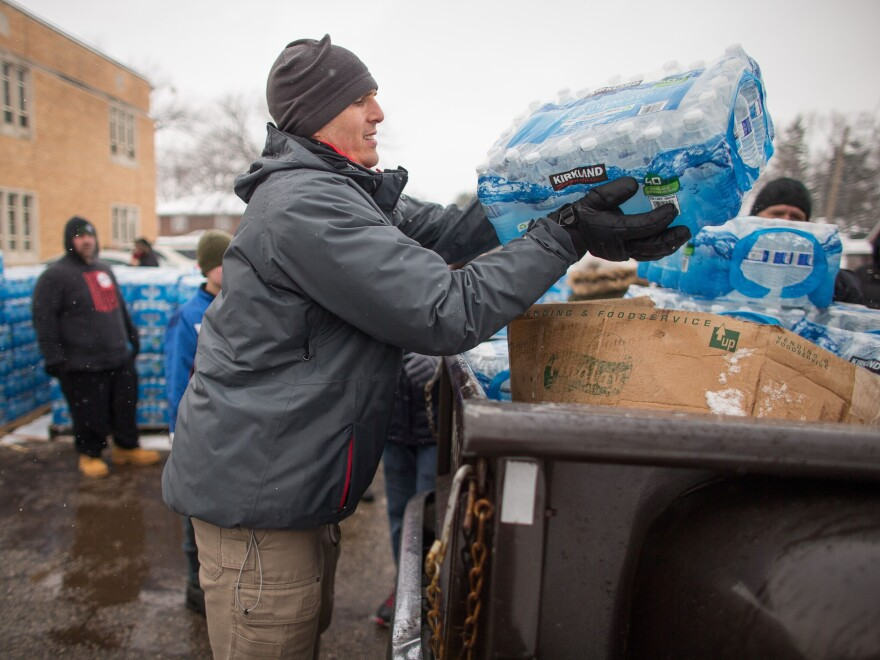 Volunteers load cases of free water into waiting vehicles at a water distribution centre at Salem Lutheran Church in Flint, Michigan, on March 5, 2016.