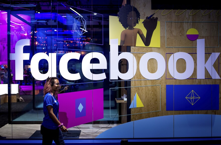A conference worker passes a demo booth at Facebook's annual F8 developer conference, on Tuesday in San Jose, Calif.