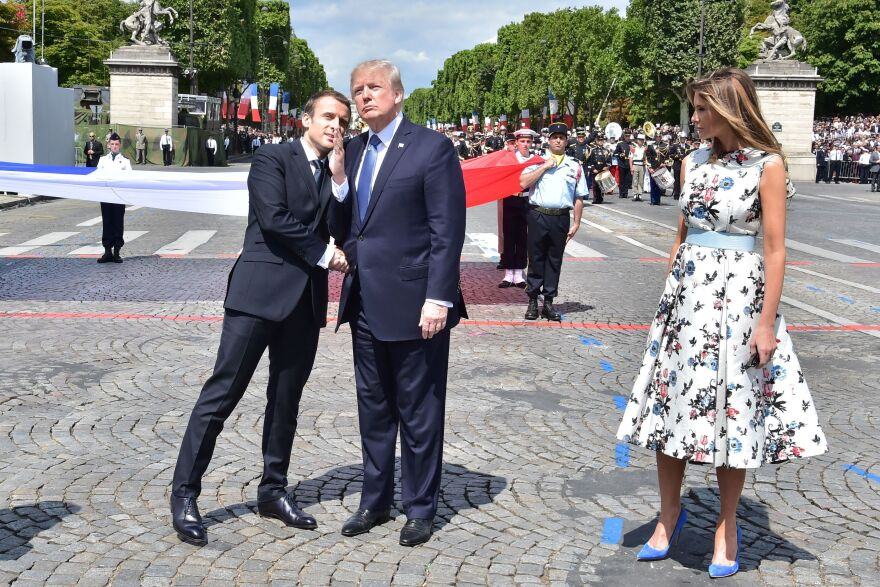 French President Emmanuel Macron (left) shakes hands with President Trump, next to first lady Melania Trump, during the annual Bastille Day military parade in Paris on July 14, 2017. Trump is hosting Macron in Washington this week for the first official state visit of his presidency.
