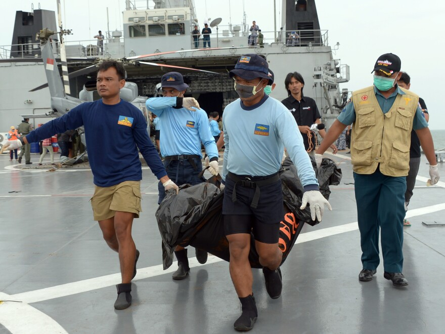 Indonesian Navy personnel carry a body bag from AirAsia Flight 8501, which crashed off the coast of Indonesian Borneo a week ago.