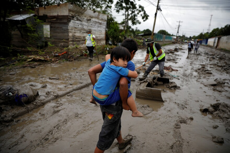 A child carries his brother down a street covered in mud after the floods caused by Hurricanes Eta and Iota.