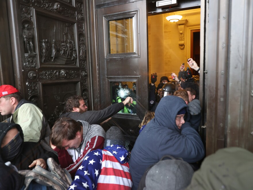 Protesters break windows and attempt to enter the U.S. Capitol Building.