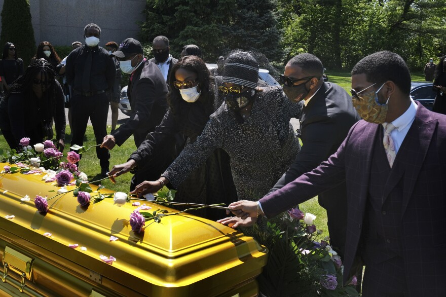 Family and friends lay flowers on the casket of Bishop Carl Williams Jr. last week at Hollywood Memorial Park and Cemetery in Union, N.J. Only a few family members were permitted to attend the service in person due to the pandemic.