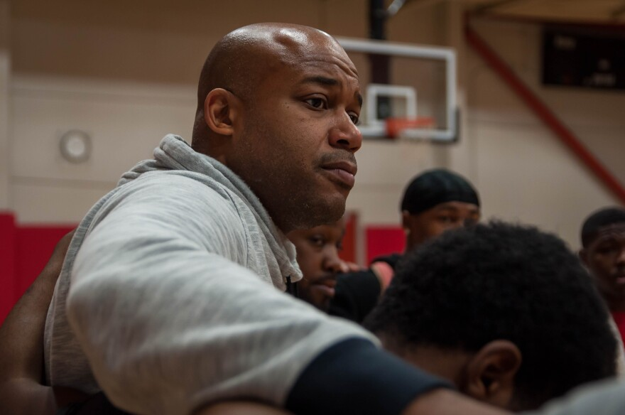 Marcus Wilson, the executive director for the Monsanto YMCA, gathers with players in their prayer circle. On Saturdays, Wilson allows players to play basketball for free to allow the players a safe space away from violence.