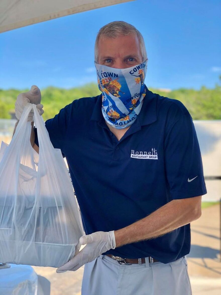 The Fort Worth restaurateur Jon Bonnell has had to ditch fine dining and take on curbside service during the coronavirus outbreak. This photo shows him masked and serving customers on Easter 2020.