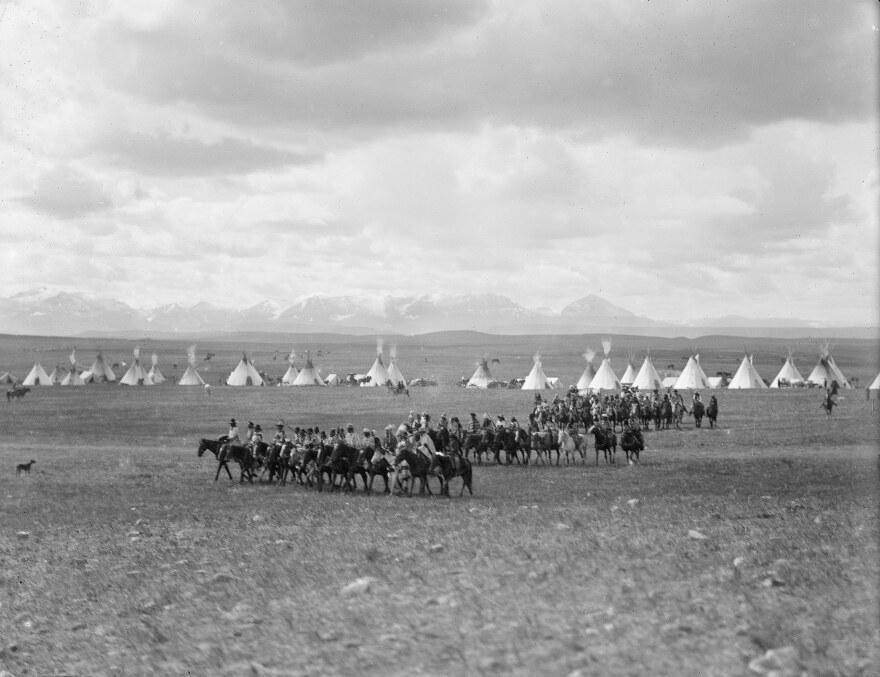 Blackfeet parade around camp before construction of the Okan lodge, 1908