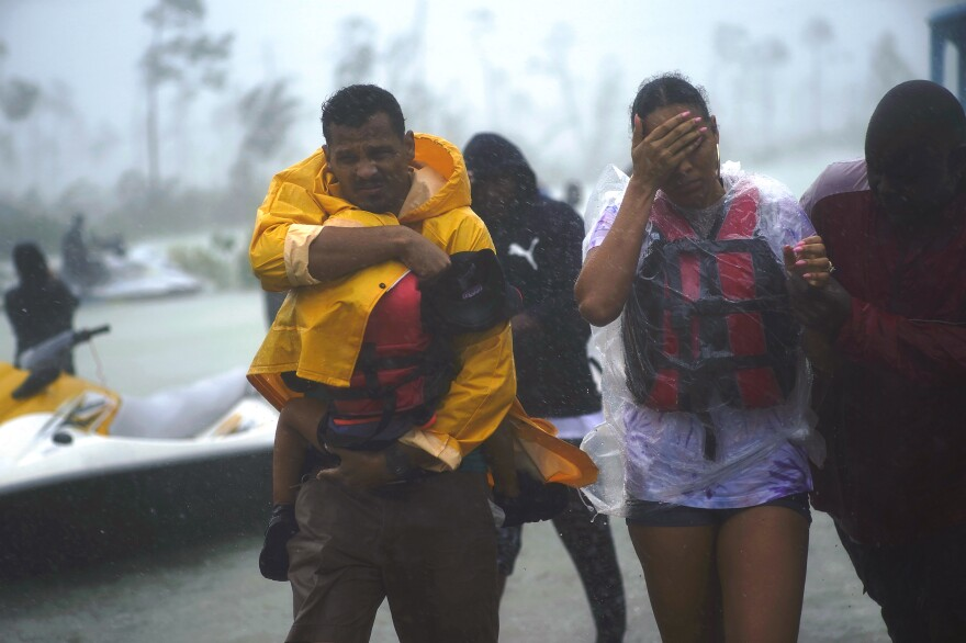 A family is escorted to a safe zone after they were rescued as Hurricane Dorian continues to rain in Freeport, Bahamas.
