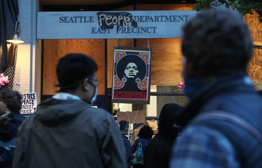 People gather near the Seattle Police Department's vacated East Precinct in the Capitol Hill occupied zone of Seattle. The open-air protest camp is more than a week old. Makeshift clinics now stand on the streets where young protesters were injured by flash-bang grenades.