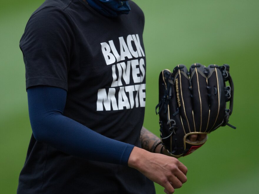 """Unidentified baseball player with glove, wearing """"Black Lives Matter"""" t-shirt."""