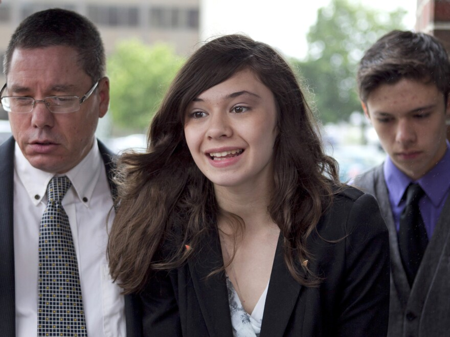 Nicole Maines, center, with her father Wayne Maines, left, and brother Jonas, speaks to reporters outside the Penobscot Judicial Center in Bangor, Maine, in June.