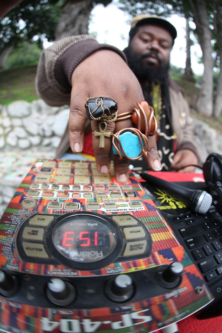 Ras G, photographed performing on his Roland SP-404, rings on hand.