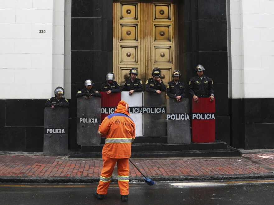 A maintenance worker sweeps the street as riot police block the door to the Congress building Tuesday in Lima. Late Tuesday night, Mercedes Aráoz, the vice president who had briefly accepted the mantle of acting president from lawmakers, performed a surprise U-turn by announcing her resignation.