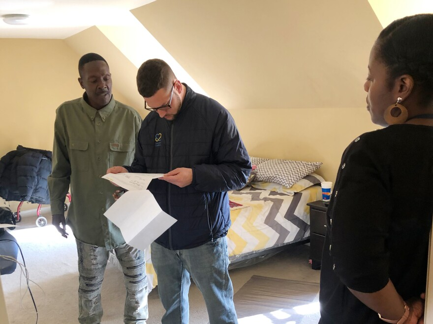Larry Moore (left) meets with Camden Coalition housing coordinator Brian Thompson and Coalition nurse Jeneen Skinner in his apartment in Camden, N.J. Having a stable housing situation, as well as getting addiction treatment dramatically reduced Moore's trips to the emergency department.
