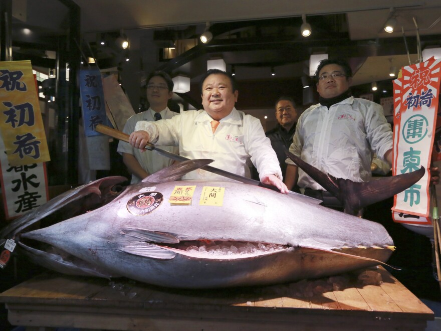 Kiyoshi Kimura (center) poses with the Pacific bluefin tuna he won for about $632,000 at the Tsukiji fish market's annual New Year auction. The fish weighs about 466 pounds.