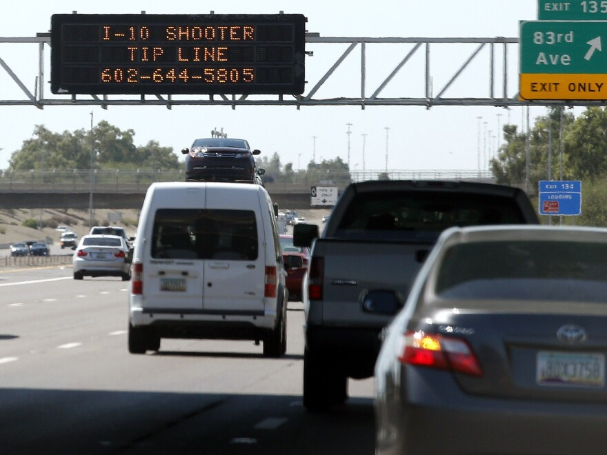 A sign displays a shooter tip line above Interstate 10 on Sept. 11 in Phoenix. Authorities have arrested a suspect in a string of freeway shootings over the past two weeks.