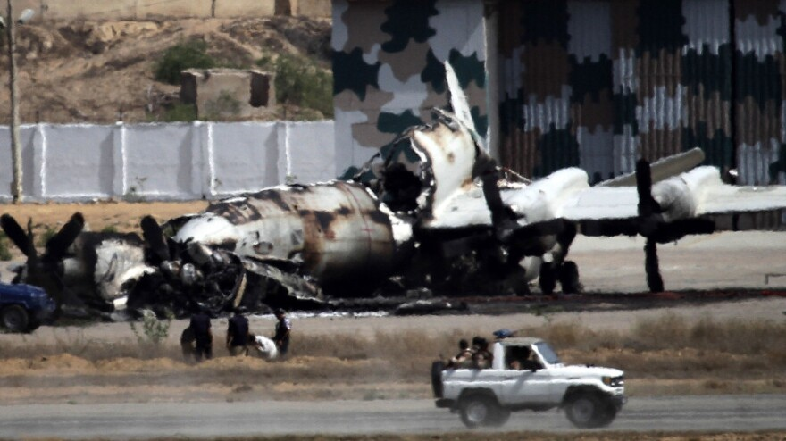 Pakistani troops drive past the wreckage of a gutted aircraft  destroyed in a militant attack on a Pakistani naval base  in Karachi on May 23.