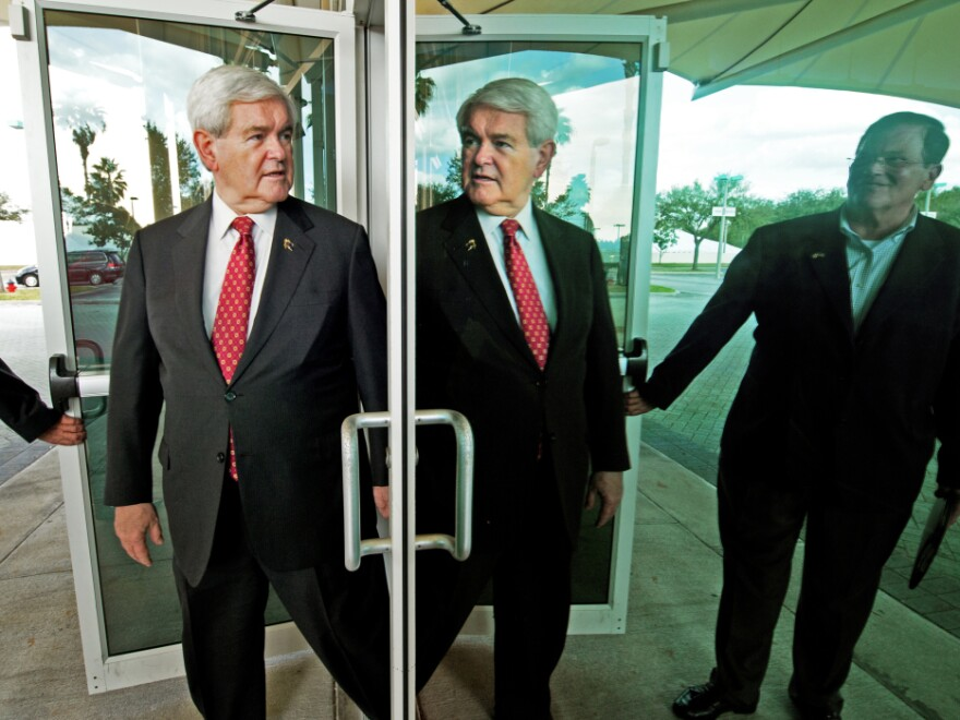 Newt Gingrich is refuting new attacks about his role at mortgage giant Freddie Mac. Gingrich's reflection is seen here as he walks out mirrored doors in Tampa, Fla. to deliver remarks and greet supporters on Jan. 23.