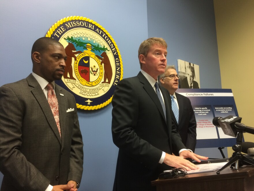 "Attorney General Chris Koster announces his lawsuit against 13 cities for violating ""Mack's Creek"" law. He was joined at his St. Louis press conference by Ferguson Commission co-chairs Starsky Wilson and Rich McClure, who have made reconfiguring municipal"