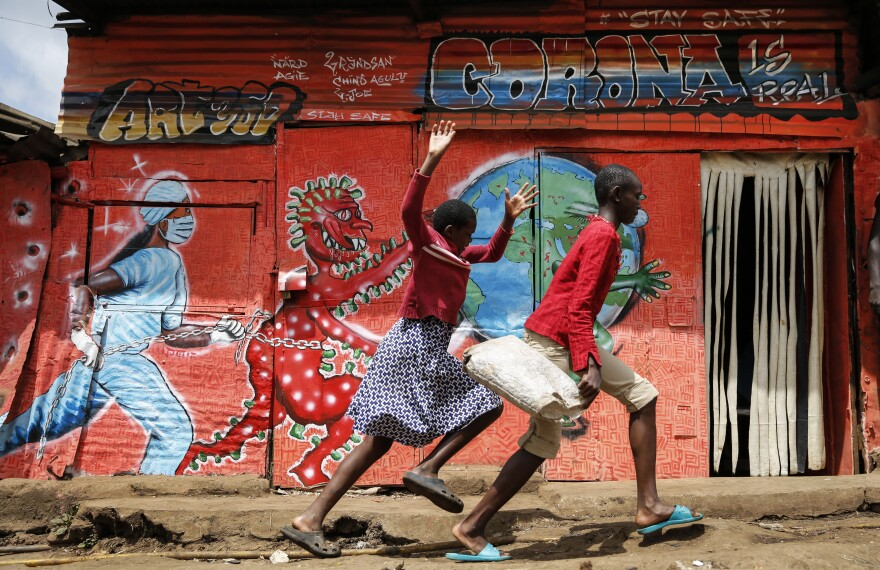 Children run down a street past an informational mural warning people about the dangers of the coronavirus in the Kibera settlement in Nairobi, Kenya, June 3.