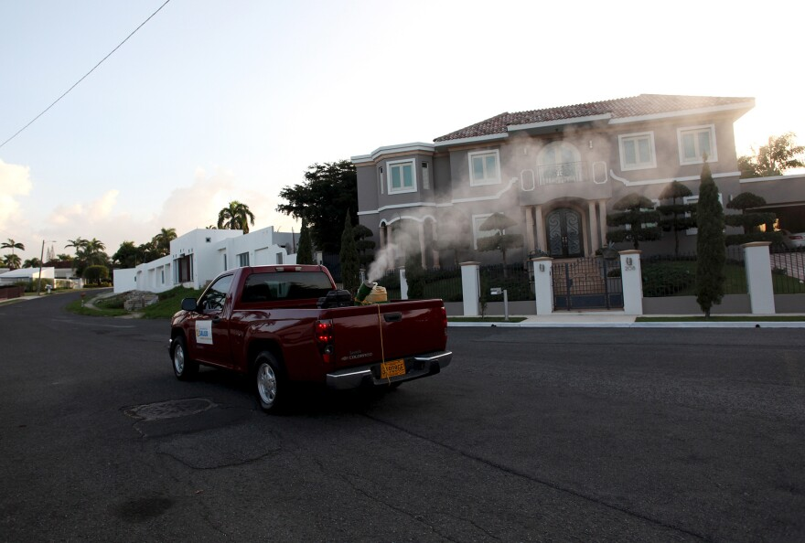 A health department pickup truck sprays insecticide against mosquitoes in a San Juan, Puerto Rico, neighborhood in January.