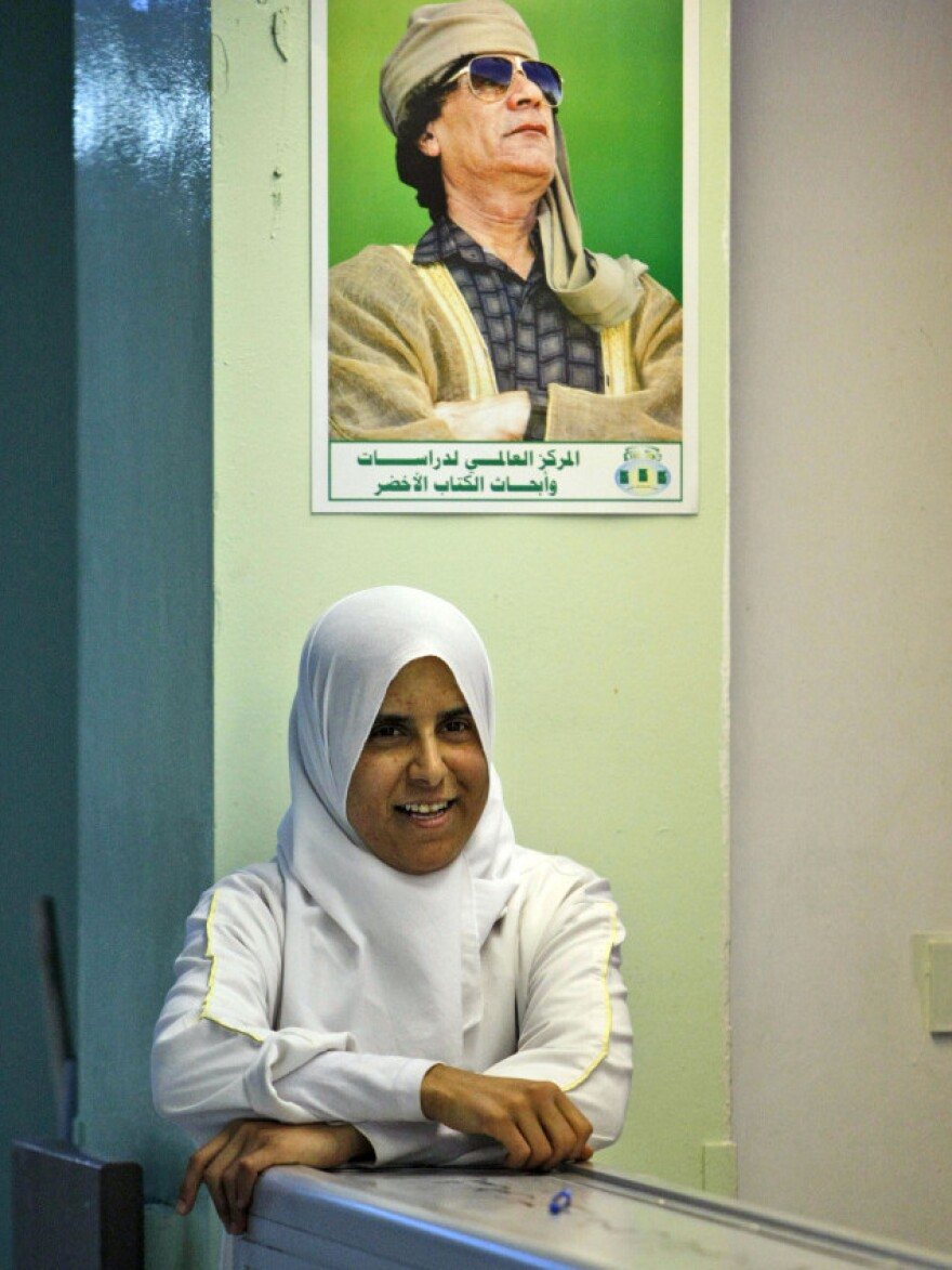 In this image taken during an organized trip by Libyan authorities, a  hospital nurse stands   in the lobby of the Zawiya teaching hospital, where rebels sought treatment during fighting. Above her, a portrait  of Libyan leader Moammar Gadhafi.