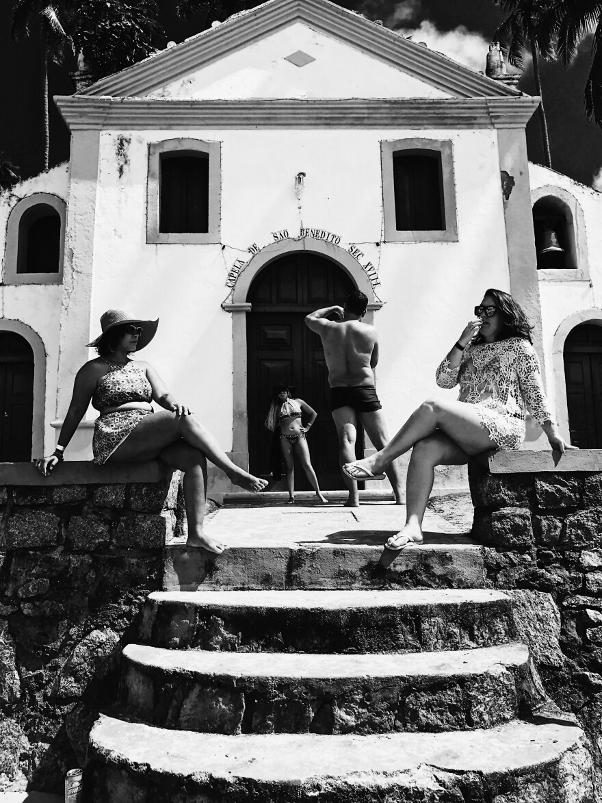 Tourists pose in front of a Catholic chapel at Carneiros Beach in Brazil.