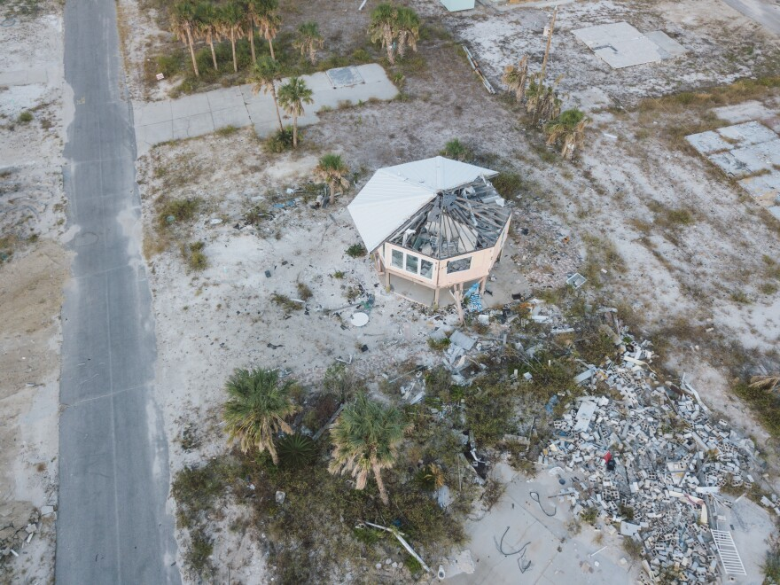 Half the roof is missing from a round house near the beach. A pile of bricks is nearby.