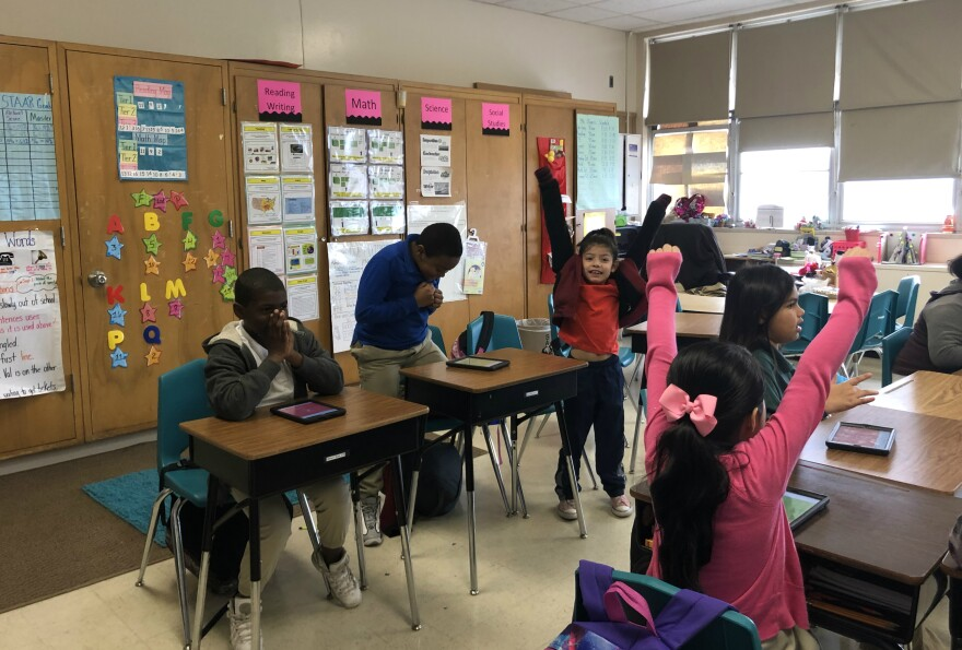 Students in Michelle Olivarri's third grade class celebrate getting the right answer on a computer game in January 2019.