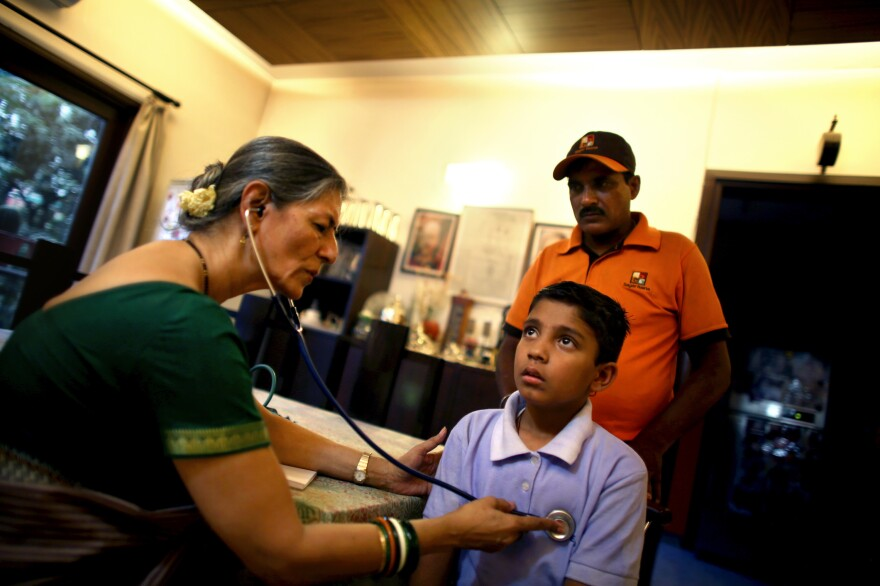 Dr. Gita Prakash (left), who runs a family clinic from her home in New Delhi, examines 10-year-old Sonu Kumar Chaudhary as his father, restaurant deliveryman Dilip Kumar Chaudhary, looks on. Prakash sees more and more cases of illness caused by the city's polluted air.