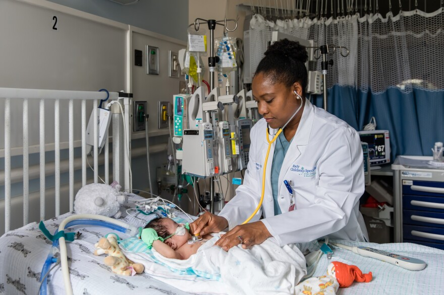 Nathaly Sweeney, a neonatologist at Rady Children's Hospital-San Diego and researcher with Rady Children's Institute for Genomic Medicine, attends to a young patient in the hospital's neonatal intensive care unit.