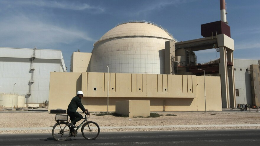 A worker rides a bicycle in front of the reactor building of the Bushehr nuclear power plant, just outside the southern city of Bushehr, Iran, in a 2010 photo.