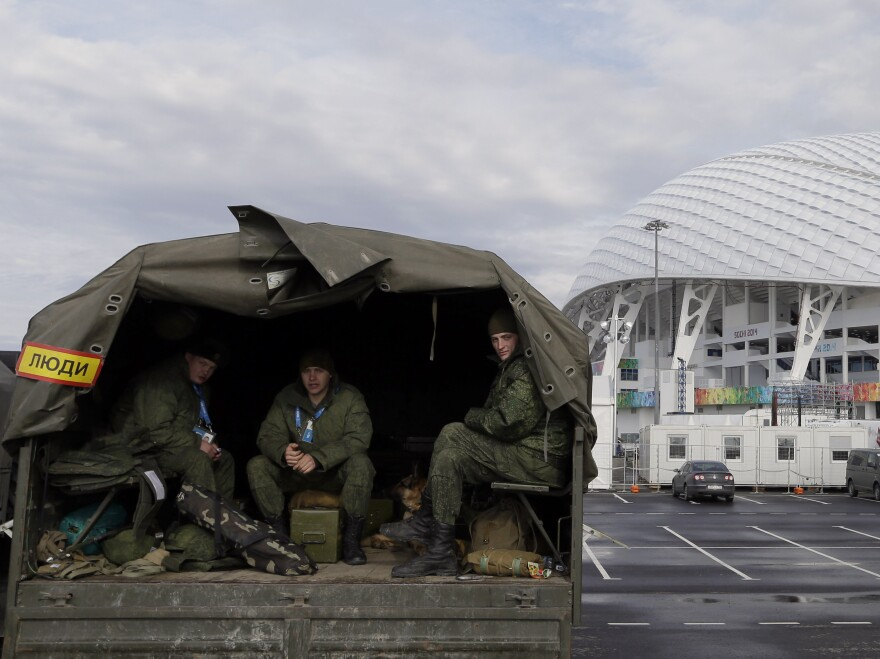 Security personnel sit in the back of a truck outside the Fisht Olympic Stadium in Sochi. Security concerns are one reason why many U.S. fans and family are not going to this year's games.