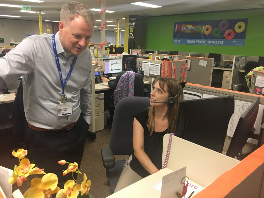 """Thomas Ylijoa, a clinic director with National Jewish Health in Denver., chats with Nichole Lopez, a tobacco cessation coach for a program there. In July, the hospital launched """"My Life, My Quit"""" a vaping cessation program aimed at teens. The program has a traditional phone helpline, but also offers coaching by text and chat."""