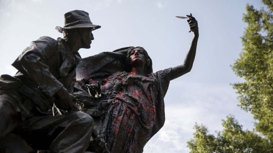 A statue of a Confederate soldier in Atlanta's Piedmont Park stands vandalized with spray paint on Monday. It was not the only Confederate monument to be vandalized in the wake of the violence in Charlottesville; a statue in Louisville, Ky., was splattered with paint too.