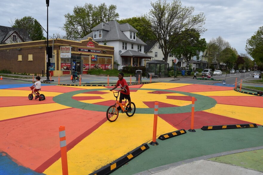 Children bike across this colorful intersection.